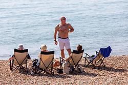"© Licensed to London News Pictures. 14/09/2020. Sussex, UK. A group of sunbathers enjoy the hot sunshine this afternoon on Brighton Beach while keeping to the ""Rule of Six"" as a mini-heatwave hits England this week with highs of 29c. Prime Minister Boris Johnson announced last week that gatherings of more than six people will be banned from today in the hope of reducing the coronavirus R number. The Rule of Six as it is known, has already become unpopular with MPs and large families for being too strict. Photo credit: Alex Lentati/LNP"