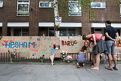 © Licensed to London News Pictures. 18/06/2017. London, UK. A family looks at posters of the missing near site of the burnt out Grenfell tower block . The blaze engulfed the 27-storey building killing dozens - with 34 people still in hospital, many of whom are in critical condition. The fire brigade say that they don't expect to find anyone else alive. Photo credit: Peter Macdiarmid/LNP