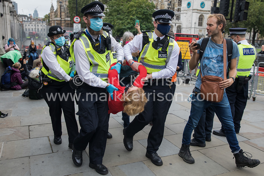 Metropolitan Police officers arrest a climate activist from Extinction Rebellion who had occupied the pavement outside the Houses of Parliament on 3 September 2020 in London, United Kingdom. Extinction Rebellion activists are attending a series of September Rebellion protests around the UK to call on politicians to back the Climate and Ecological Emergency Bill (CEE Bill) which requires, among other measures, a serious plan to deal with the UK's share of emissions and to halt critical rises in global temperatures and for ordinary people to be involved in future environmental planning by means of a Citizens' Assembly.