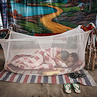 Early in the morning of the goddess Mazu's birthday celebration, a man sleeps upon the opera theater stage in Wenxing village, Meizhou Island, Fujian province, China.
