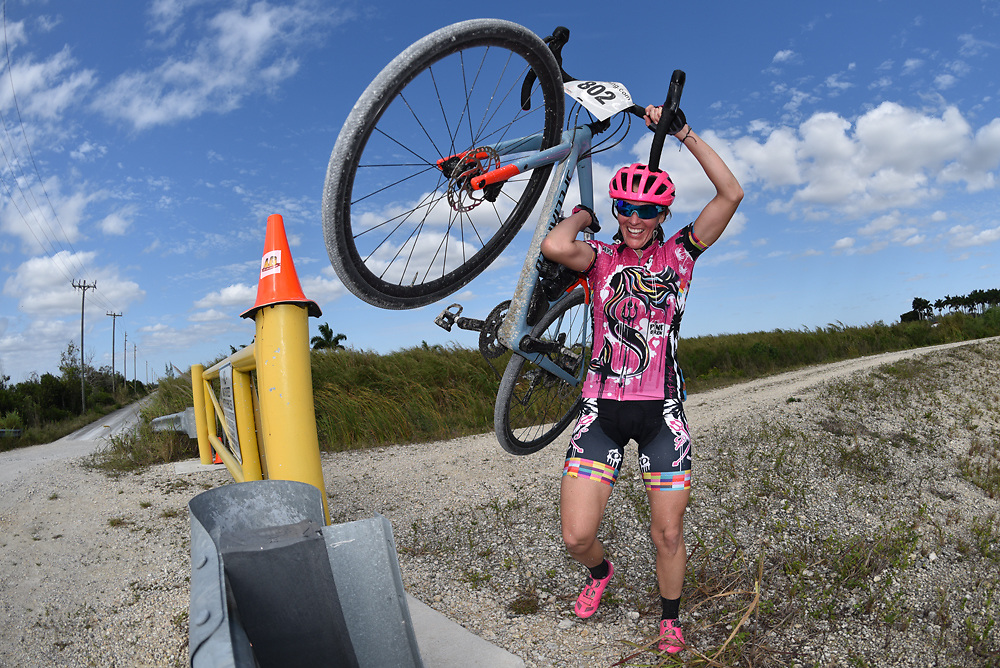 A gravel bike racer dismounts at a barricade