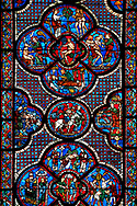 Medieval stained glass Window of the Gothic Cathedral of Chartres, France - dedicated to the Good Samaritan .  Bottom central panel shows A bandit prepares to attack the pilgrim , below left -The pilgrim leaving Jerusalem, right -  The pilgrim is beaten, robbed and stripped , above - A Priest and a Levite see the injured man but walk on past. Central oval panel - The Samaritan leading the Pilgrim to an inn, left of this - A Samaritan binds the injured man's wounds, right of centre - An innkeeper welcoming the Samaritan. Top central panel shows Adam dwelling in Paradise, below - At the inn, the Samaritan nurses the injured man back to health, left - God breathing life into Adam, above - God warning Adam and Eve not to eat from the tree of knowledge, right - God creates Eve out of Adam's rib . A UNESCO World Heritage Site. .<br /> <br /> Visit our MEDIEVAL ART PHOTO COLLECTIONS for more   photos  to download or buy as prints https://funkystock.photoshelter.com/gallery-collection/Medieval-Middle-Ages-Art-Artefacts-Antiquities-Pictures-Images-of/C0000YpKXiAHnG2k
