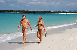 Couple wearing swimming costumes walking along the beach near Guardalavaca; Holguin province; Cuba,