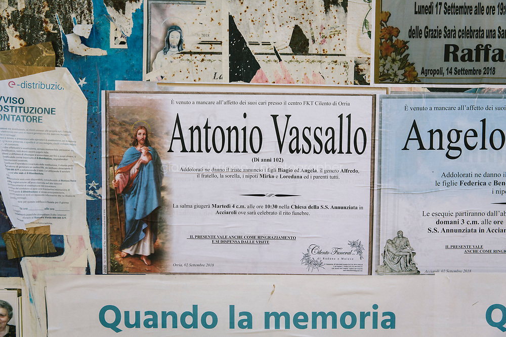 ACCIAROLI, ITALY - 14 SEPTEMBER 2018: The obituary poster for Antonio Vassallo, who died at 102 years old in September 2018 in Acciaroli, a small fishing village in the municipality of Pollica, Italy, on September 14th 2018.<br /> <br /> To understand how people can live longer throughout the world, researchers at University of California, San Diego School of Medicine have teamed up with colleagues at University of Rome La Sapienza to study a group of 300 citizens, all over 100 years old, living in Acciaroli (Pollica), a remote Italian village nestled between the ocean and mountains in Cilento, southern Italy.<br /> <br /> About 1-in-60 of the area's inhabitants are older than 90, according to the researchers. Such a concentration rivals that of other so-called blue zones, like Sardinia and Okinawa, which have unusually large percentages of very old people. In the 2010 census, about 1-in-163 Americans were 90 or older.