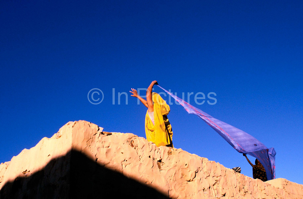 Two girls dry washing on the roof of their house aided by the desert winds. Chinguetti, Mauritania. Chinguetti was a 'ksar' or medieval trading centre that was founded in the 6th century and for centuries the city was a principal gathering place for pilgrims of the Maghrib to gather on the way to Mecca. It is known for it's ancient libraries full of priceless books and Korans and is said to be the seventh holiest city in Islam