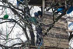 Denham, UK. 22nd March, 2021. Anti-HS2 activists at Denham Ford Protection Camp observe bailiffs from the National Eviction Team (NET) from a tree house very high up in a tree in Denham Country Park during a large security operation by the National Eviction Team (NET) and Thames Valley Police to dismantle a makeshift tower occupied by fellow activists seeking to delay electricity pylon relocation works by Babcock in connection with the HS2 high-speed rail link.