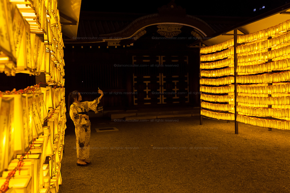 A Japanese women in kimono tkes a selfie with the spectacular lanterns display during the Mitama matsuri at the controversial Yasukuni Shrine in Kudanshita, Tokyo, Japan. Friday July 14th 2017. The Mitama Matsuri is one of Japan's largest Obon festivals with over 300,000 visiting the shrine to pay respect to ancestors during the 4 days it lasts. Obon is festival of remembrance for ancestors who are believed to come back from the other world and visit the living at this time. Yasukuni Shrine, which houses the spirits of the Japanese war dead, celebrates these spirits with 30,00 yellow lanterns and mikoshi parades and traditional dancing. The festivals runs from July 13th to 16th.