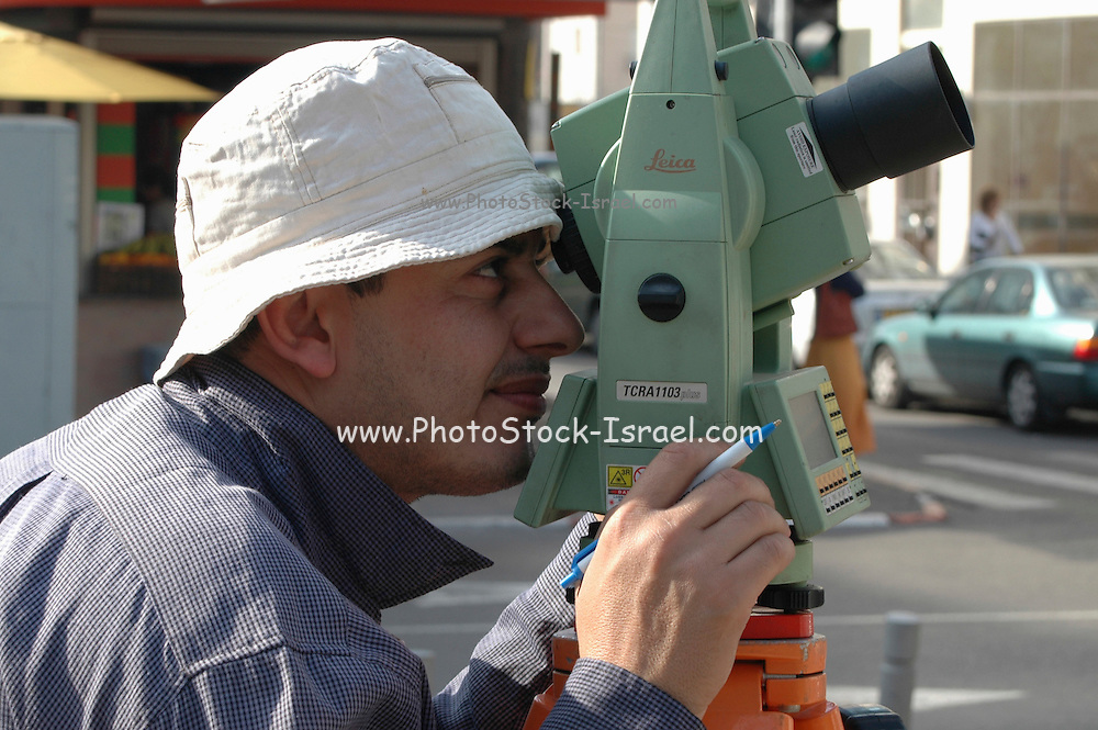 male surveyor looking through his Lieca optical tool