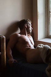 naked man in bed looking out a window
