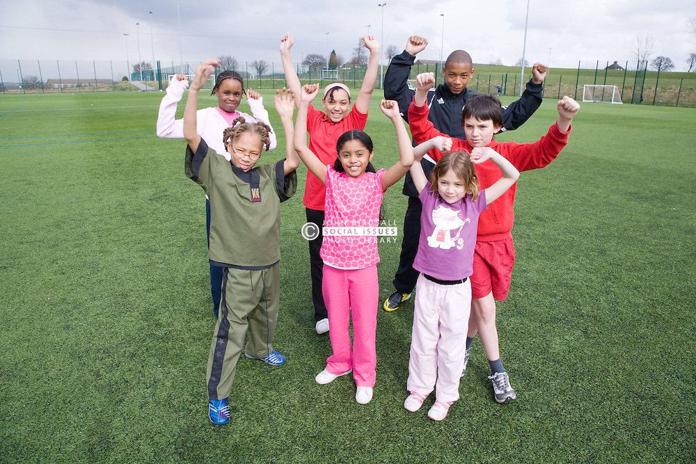 Group of children having fun on a playing field at their local leisure centre,