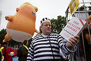 Lookalike Boris Johnson holding a copy of The Mueller Report near the Trump Baby, a six metre high inflatable blimp flying above Westminster prior to protests against the state visit of US President Donald Trump on 4th June 2019 in London, United Kingdom. Organisers Together Against Trump which is a collaboration between the Stop Trump Coalition and Stand Up To Trump, have organised a carnival of resistance, a national demonstration to protest against President Trump's policies and politics during his official UK visit.
