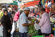 Muslim couple are customers at the famous Ballero street market for vegetables and other fresh food in Palermo, Sicily, Italy