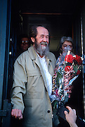 Russian Nobel prize novelist Alexander Solzhenitsyn smiles after arriving by train returning to his homeland as his wife Alya Svetlova looks on June 5, 1994 in Khabarovsk, Russia. Solzhenitsyn was expelled from the Soviet Union in 1974 but returned after the fall of the Soviet Union.
