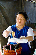 Hmong worker dishing up food in festival kitchen. Hmong Sports Festival McMurray Field St Paul Minnesota USA