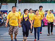 05 DECEMBER 2014 - BANGKOK, THAILAND:  Thais wearing yellow walk to Sanam Luang for observances of the King's Birthday. Thais marked the 87th birthday of Bhumibol Adulyadej, the King of Thailand, Friday. The King was born on December 5, 1927, in Cambridge, Massachusetts. Thais wear yellow on the King's birthday because yellow is considered the King's color. The King was born on a Monday and yellow is the color assigned to Monday. The family was in the United States because his father, Prince Mahidol, was studying Public Health at Harvard University. He has reigned since 1946 and is the world's currently reigning longest serving monarch and the longest serving monarch in Thai history. Bhumibol, who is in poor health, is revered by the Thai people. His birthday is a national holiday and is also celebrated as Father's Day. He is currently hospitalized in Siriraj Hospital, recovering from a series of health setbacks.    PHOTO BY JACK KURTZ