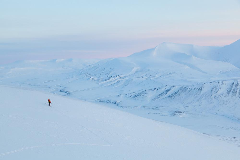 Mylène Jacquemart skies across a small plateau at dusk in Koslådalen, Svalbard.