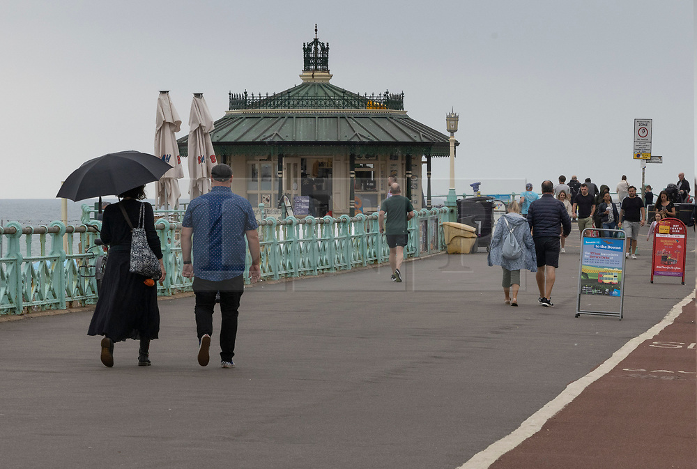 © Licensed to London News Pictures. 24/07/2021. Brighton, UK. Mixed weather on the sea front at Brighton on the south coast. The weather has changed for most places today with rain and lightning forecast. Photo credit: Peter Macdiarmid/LNP