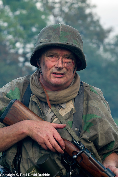 A Re-enactor portrayiing a panzer grenadier from the Grossdeutschland division wearing a Splinter Pattern camouflage smock, Y-straps, Stahlhelm and carrying a Mauser K98 Rifle  during a battle battle re-enactment in on Pickering Showground<br /> <br /> 17/18 October 2015<br />  Image © Paul David Drabble <br />  www.pauldaviddrabble.co.uk