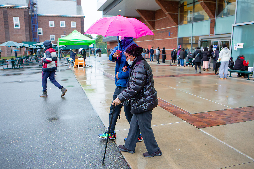 Brooklyn, NY - 1 November 2020. Voters in Brooklyn's Midwood neighborhood stood in line in a light rain at a polling place in Brooklyn College to cast their ballots on the last day of early voting in the 2020 presidential election in New York.  A woman with a cane is helped out after voting.