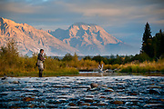 Fisherman at sunrise along the Snake River with Grand Teton National Park's Mount Moran in the distance.