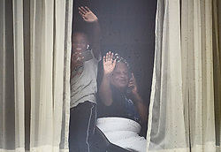 © Licensed to London News Pictures. 16/02/2021. London, UK. A woman and child wave from the window of their hotel room at the Radisson Hotel near Heathrow Airport, where travellers from red list countries are being held in quarantine. New quarantine measures have been introduced for travellers form red list countries, who will be required to isolate for ten days in a hotel at a cost of £1,750 per person. Photo credit: Ben Cawthra/LNP