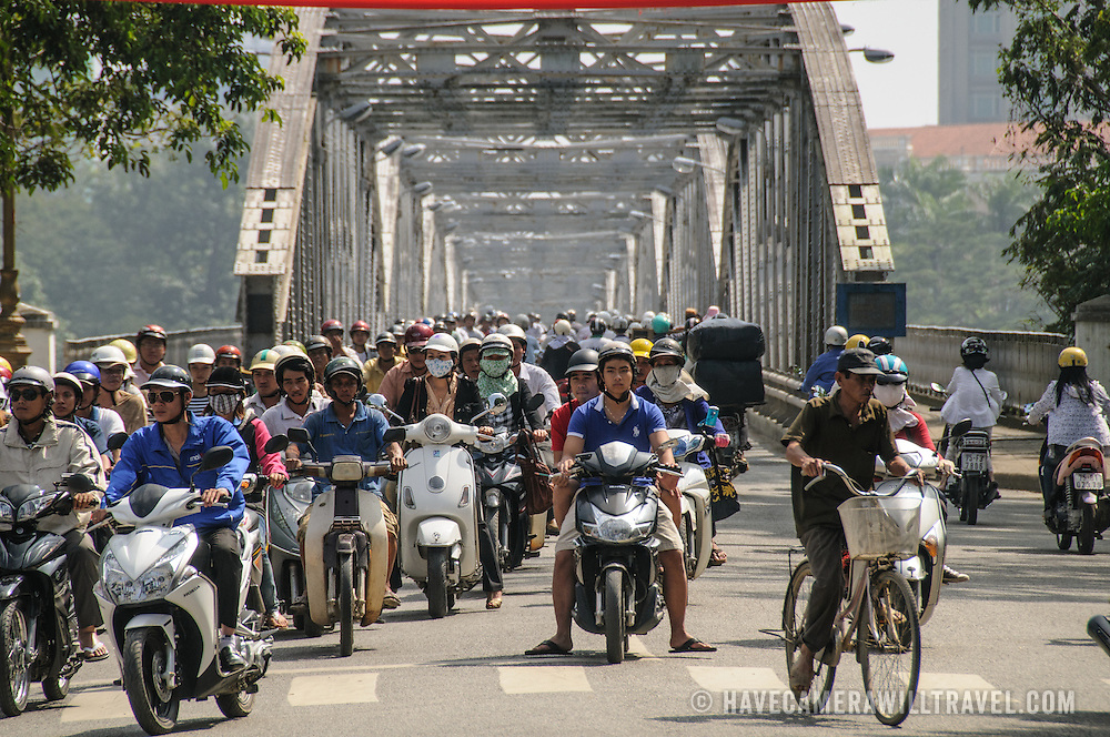 Hundreds of scooters and bikes crossing Cau Truong Tien in traffic in Hue, Vietnam.