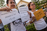 """12 JANUARY 2014 - BANGKOK, THAILAND:  Pro-democracy advocates hold up signs before a candlelight vigil at Thammasat University in Bangkok. About 500 people from all walks of Thai life came to a candlelight vigil at Thammasat University. They prayed for a peaceful resolution to the political conflict in Thailand. They finished the vigil by singing the John Lennon song """"Imagine."""" Anti-government protestors are expected """"Shutdown Bangkok"""" Monday. There were reports Sunday evening that some intersections were already being blocked.      PHOTO BY JACK KURTZ"""