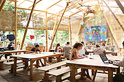 """Secondary school students studying academic subjects in the secondary school area<br /><br />The Green School (Bali) is one of a kind in Indonesia. It is a private, kindergarten to secondary International school located along the Ayung River near Ubud, Bali, Indonesia. The school buildings are of ecologically-sustainable design made primarily of bamboo, also using local grass and mud walls. There are over 600 students coming from over 40 countries with a percentage of scholarships for local Indonesian students.<br /><br />The impressive three-domed """"Heart of School Building"""" is 60 metres long and uses 2500 bamboo poles. The school also utilizes renewable building materials for some of its other needs, and almost everything, even the desks, chairs, some of the clothes and football goal posts are made of bamboo.<br /><br />The educational focus is on ecological sustainability. Subjects taught include English, mathematics and science, including ecology, the environment and sustainability, as well as the creative arts, global perspectives and environmental management. This educational establishment is unlike other international schools in Indonesia. <br /><br />Renewable energy sources, including solar power and hydroelectric vortex, provide over 50% of the energy needs of the school. The school has an organic permaculture system and prepares students to become stewards of the environment. <br /><br />The school was founded by John and Cynthia Hardy in 2008."""