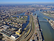 "Nederland, Noord-Holland, Amsterdam; 23-03-2020; Piet Heinkade met emplacement van de NS (Rietlanden). Oostelijke eilanden met IJhaven en Veemkade, Dijksgracht (links).<br /> Door de Coronacrisis is er weinig verkeer en omdat de NS een speciale basisdienstregeling ingevoerd, zijn veel treinen 'geparkeerd' op opstelsporen. <br /> Piet Heinkade with railway yard of the NS (Rietlanden). Eastern islands with IJhaven and Veemkade, Dijksgracht (right).<br /> Due to the Corona crisis, there is little traffic and because the NS has introduced a special basic timetable, many trains are ""parked"" on Railway yard.<br /> <br /> luchtfoto (toeslag op standaard tarieven);<br /> aerial photo (additional fee required)<br /> copyright © 2020 foto/photo Siebe Swart"