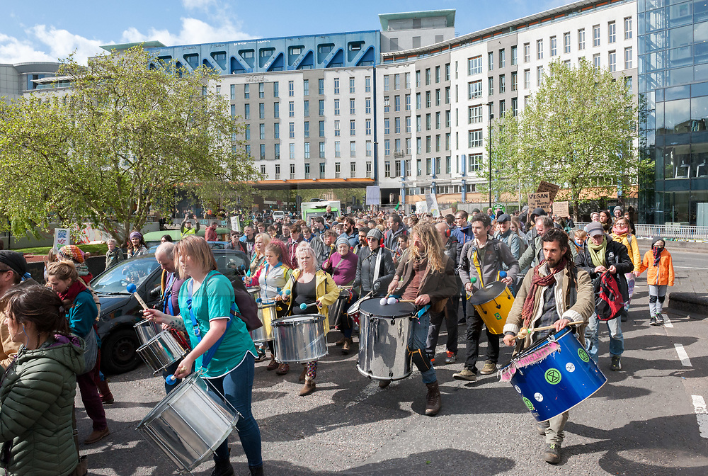 """© Licensed to London News Pictures. 27/04/2019. Bristol, UK. Earth Day Climate Protest and Bristol Bearpit Takeover by Earth Strike UK with marchers blocking roads and holding up traffic in Bristol city centre. The event was held on the weekend after Earth Day, holding protests across the country over climate change and against pollution to symbolise the halfway mark to the Earth Strike. The Bristol event had free music, food, workshops and was located at the """"Bearpit"""" St James Barton roundabout, a major road junction in the city centre with a sunken roundabout which is currently partly squatted. The campaign is against new pipelines, airports and fracking sites, and wants sustainable energy, clean water, decent housing and respect for all people. Photo credit: Simon Chapman/LNP"""