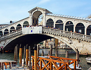 The Rialto Bridge (Italian: Ponte di Rialto) is one of the four bridges spanning the Grand Canal in Venice, Italy. It is the oldest bridge across the canal, and was the dividing line for the districts of San Marco and San Polo. The present stone bridge, a single span designed by Antonio da Ponte, was finally completed in 1591.