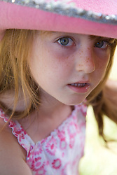 Little girl looking up from under a hat,