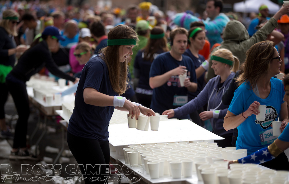 Volunteers ready cups of water for the throngs at a water station on Fell Street during the 103rd running of the Bay to Breakers 12K race, Sunday, May 18, 2014 in San Francisco. (Photo by D. Ross Cameron)