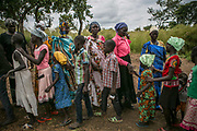 Nyakuoth Deng, 32, center, shakes hands with children after the church service inside Bidibidi refugee settlement in Uganda. She was raped by seven Dinka soldiers as she was running towards the UN compound in Juba in December 2013. She came to Uganda with her three children, but has not heard about her husband.
