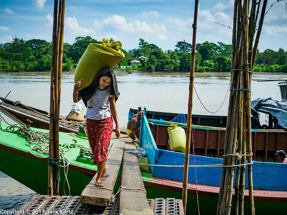 "21 NOVEMBER 2017 - WAKEMA, AYEYARWADY REGION, MYANMAR:  A woman carries a sack of paddy rice (unharvested rice) off a barge in the Ayeyarwady  Delta. Most of the rice is still moved by barge because of the lack of roads in the area. Myanmar is the world's sixth largest rice producer and more than half of Myanmar's arable land is used for rice cultivation. The Ayeyarwady Delta is the most important rice growing region and is sometimes called ""Myanmar's Granary."" The UN Food and Agriculture Organization (FAO) is predicting that the 2017 harvest will increase over 2016 and that exports will surge to 1.8 million tonnes.  PHOTO BY JACK KURTZ"