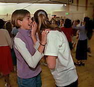 Katie Meagher 11, left, shares a secret with her friend Annabelle Ostrander,11,  right, (both in 6th grade) during a lunchtime dance at Crocker Riverside Elementary School, Friday, March 23, 2001.  The event, planned by the school's student council for the 5th and 6th grade classes, was eagerly anticipated by many of the students for weeks.