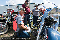 AMCA judge Ken Harvey (seated) with chief judge Don Dzurick and Laura Tinker Fritz as they scrutinize a great looking Harley-Davidson Panhead at the AMCA (Antique Motorcycle Club of America) Sunshine Chapter National Meet in New Smyrna Beach during Daytona Beach Bike Week. FL. USA. Saturday March 11, 2017. Photography ©2017 Michael Lichter.