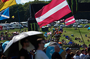 Pauls Jonass sails past the flags of Latvia and others at the grand prix of Great Britain at Matterley Basin.