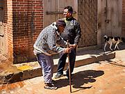 12 MARCH 2017 - BHAKTAPUR, NEPAL: A man helps an elderly man walk down a street in Bhaktapur.     PHOTO BY JACK KURTZ