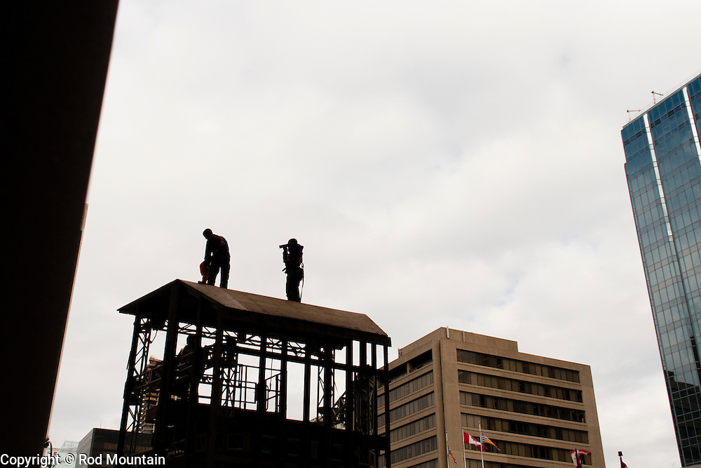 The silhouette of workmen as seen at a construction site downtown Vancouver.