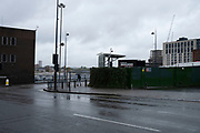 Empty area of the wholesale markets precinct, which is partially used as a parking lot, in Birmingham city centre, which is virtually deserted under Coronavirus lockdown on a wet rainy afternoon on 28th April 2020 in Birmingham, England, United Kingdom. Britains second city has been in a state of redevelopment for some years now, but with many outdated architectural remnants still remaining, on a grey day, the urban landscape appears as if frozen in time. Coronavirus or Covid-19 is a new respiratory illness that has not previously been seen in humans. While much or Europe has been placed into lockdown, the UK government has put in place more stringent rules as part of their long term strategy, and in particular social distancing.