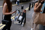 Young women shoppers on Neal Street and a mirrored sign for fashion retailer Subdued, on 12th July 2021, in London, England. Subdued is an Italian brand .. for fun-loving, strong and independent teenagers. Founded in the 90's they have 130 stores around the world.
