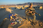 Curtis Newcomer, a U.S. Army soldier, with his typical day's worth of food at the National Training Center at Fort Irwin in California's Mojave Desert. (From the book What I Eat: Around the World in 80 Diets.) The caloric value of his day's worth of food in the month of September was 4,000 kcals. He is 20 years old; 6 feet, 5 inches tall; and 195 pounds. During a two-week stint before his second deployment to Iraq, he spends 12-hour shifts manning the radio communication tent (behind him). He eats his morning and evening meals in a mess hall tent, but his lunch consists of a variety of instant meals in the form of MREs (Meals, Ready-to-Eat). His least favorite is the cheese and veggie omelet. ?Everybody hates that one. It's horrible,? he says. A mile behind him, toward the base of the mountains, is Medina Wasl, a fabricated Iraqi village?one of 13 built for training exercises, with hidden video cameras and microphones linked to the base control center for performance reviews.  MODEL RELEASED.