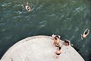 Nederland, Nijmegen, 25-6-2020 Mensen, vooral jongeren, trekken massaal naar de oevers van de waal en de spiegelwaal in het rivierpark aan de overkant van Nijmegen . De warmte, hoge temperatuur, drijft mensen naar het water . Duiken vanaf een brugpijler . Het is verboden in de rivier te zwemmen vanwege de stroming het het drukke scheepvaartverkeer . . Foto: ANP/ Hollandse Hoogte/ Flip Franssen
