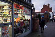 Small business shop front selling beauty and hair products at night in the Kings Heath area of Birmingham, United Kingdom. Kings Heath is a suburb of Birmingham, three miles south of the city centre. It is the next suburb south from Moseley.