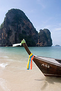 Longtail boat at Phra Nang Bay, Railay. This pure white sand beach is surrounded by spectacular limestone cliffs. Central in the bay stands Phra Nang's distinctive rock, looming over the bay dramatically.