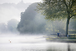 © Licensed to London News Pictures. 24/05/2021. Henley-On-Thames, UK. A man jogging along the riverbank, surrounded by a mist covered landscape, in the early morning on the River Thames at Henley-on-Thames in Oxfordshire . Photo credit: Ben Cawthra/LNP