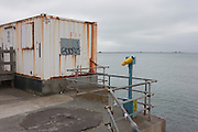 A rusting First Aid container hut and a telescope pointing to the sky instead of the sea, on the Western Esplanade at Southend.