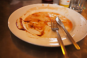 The remnants of a finished full English breakfast on a plate in a 'greasy spoon' cafe. Also known as a caf, these places provide breakfast and cheap food all day. This meal and these cafes are somewhat of a British institution.