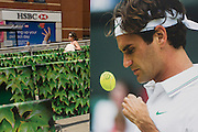 Day 2 of the annual lawn tennis championships and spectators queue for taxies be a poster of past Mens' champion Roger Federer outside the mainline and underground (subway) station in the south London suburb. The Wimbledon Championships, the oldest tennis tournament in the world, have been held at the nearby All England Club since 1877.